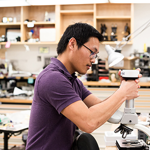 """young man repairing a microscope at the uc davis microscope services workshop"""