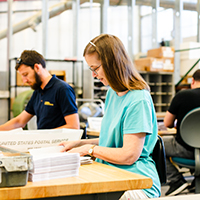"""man and woman working in the uc davis mail services center"""