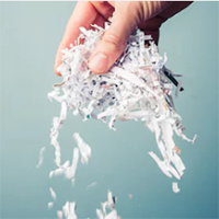 """hand dropping a bunch of shredded paper"""