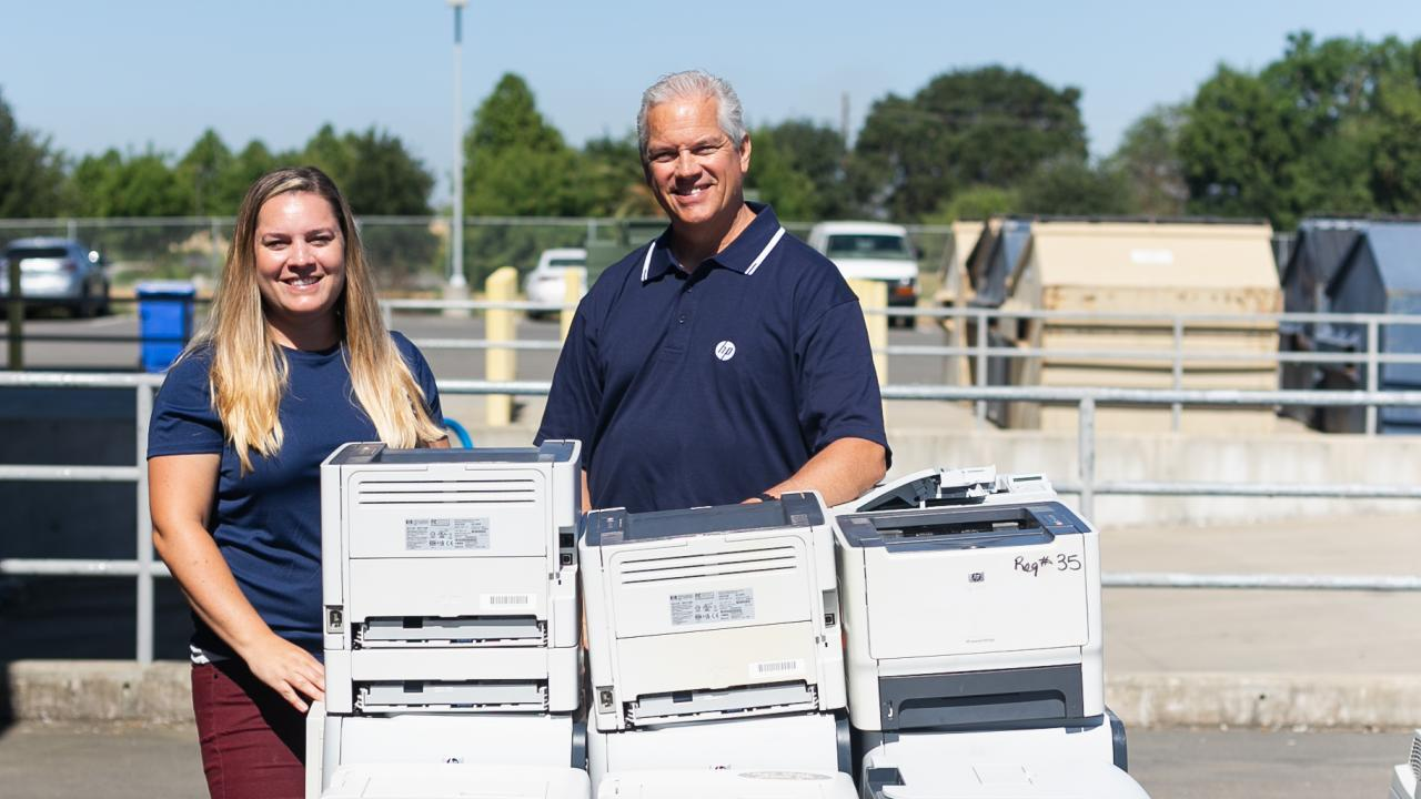 two uc davis employees stand alongside a pile of printers as part of the HP printer exchange event