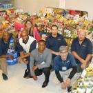 Mail Services employees pose by food donations