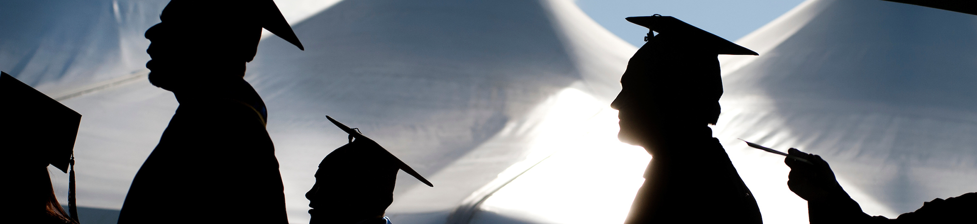 silhouette of faculty members in caps and gowns